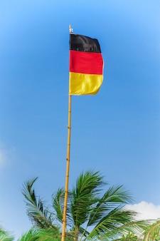 Bandera alemana ondeando al viento sobre un fondo de cielo azul extreme closeup.