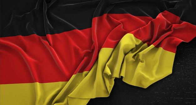 Bandera de alemania arrugado sobre fondo oscuro 3d render