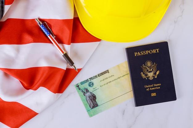 Bandera americana en cheque de ayuda financiera de estímulo para el pasaporte de estados unidos en casco