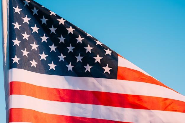 Bandera americana en un cielo azul, de cerca. símbolo del día de la independencia del cuatro de julio en estados unidos.