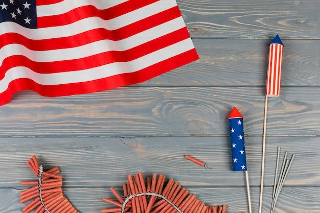 Bandera americana y fuegos artificiales de vacaciones sobre fondo de madera