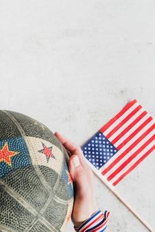 Bandera americana y mano con baloncesto.
