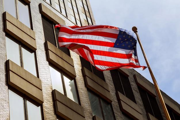 Bandera americana ondeando contra dos rascacielos y un cielo azul.