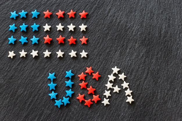 Bandera americana y palabra usa concepto 4 de julio día de la independencia. fondo de pizarra. copia espacio