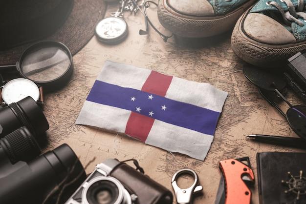 Bandera de las antillas holandesas entre los accesorios del viajero en el viejo mapa vintage concepto de destino turístico.