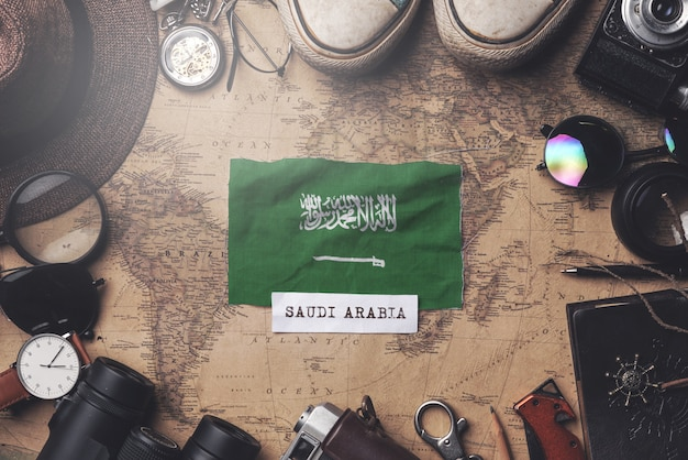 Bandera de arabia saudita entre los accesorios del viajero en el viejo mapa vintage. tiro de arriba