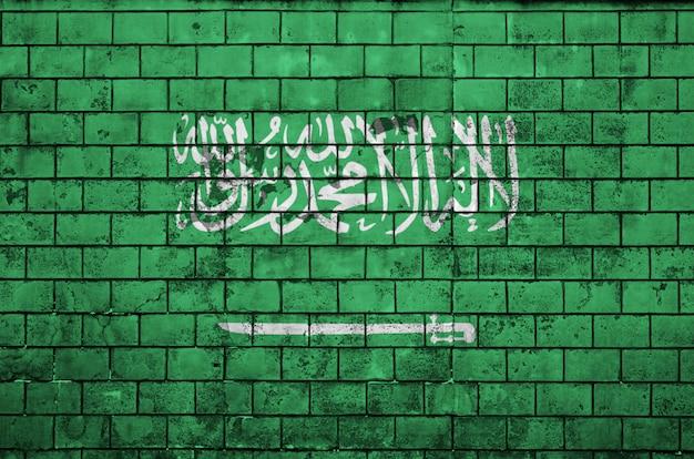 La bandera de arabia saudita está pintada en una vieja pared de ladrillos