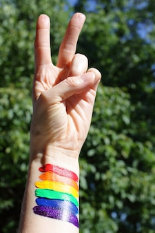 Bandera del arco iris del mes del orgullo lgbt 2020 con concepto de mano de victoria