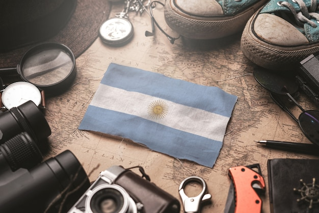Bandera argentina entre los accesorios del viajero en el viejo mapa vintage. concepto de destino turístico.