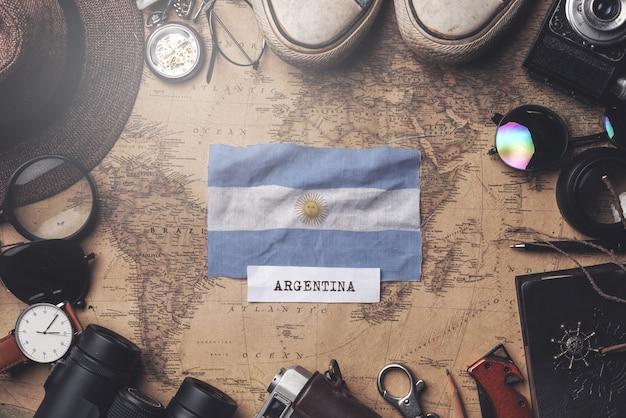 Bandera argentina entre los accesorios del viajero en el viejo mapa vintage. tiro de arriba