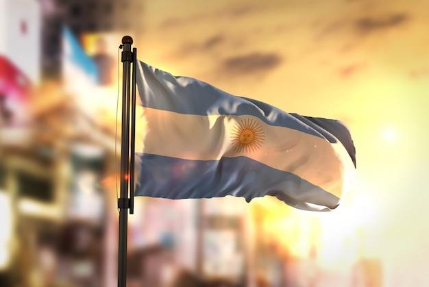 Bandera de la argentina contra la ciudad borrosa de fondo en sunrise backlight