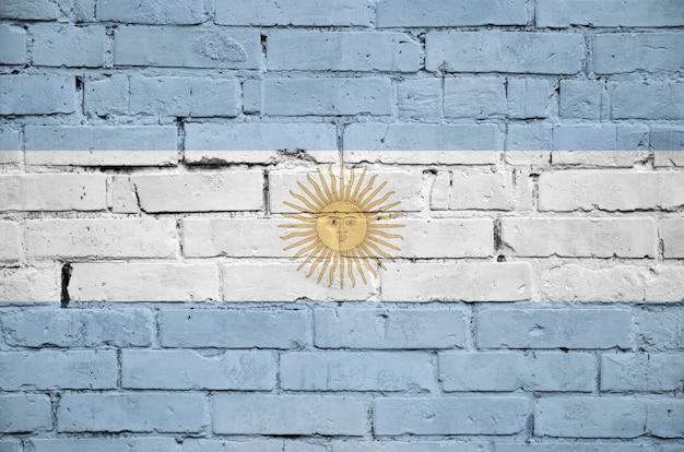 La bandera argentina está pintada en una vieja pared de ladrillos