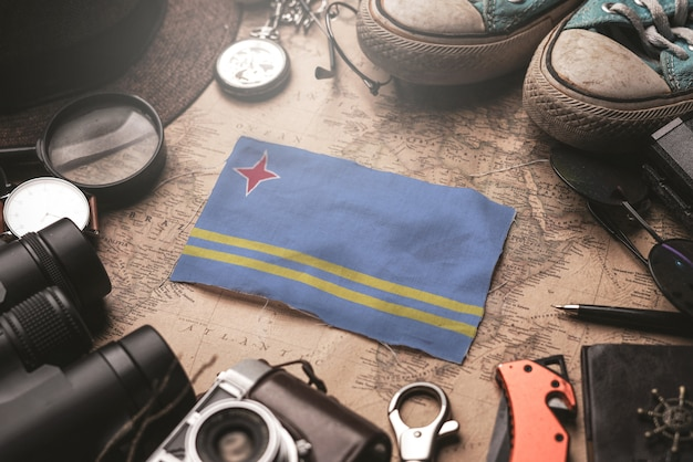 Bandera de aruba entre los accesorios del viajero en el viejo mapa vintage. concepto de destino turístico.