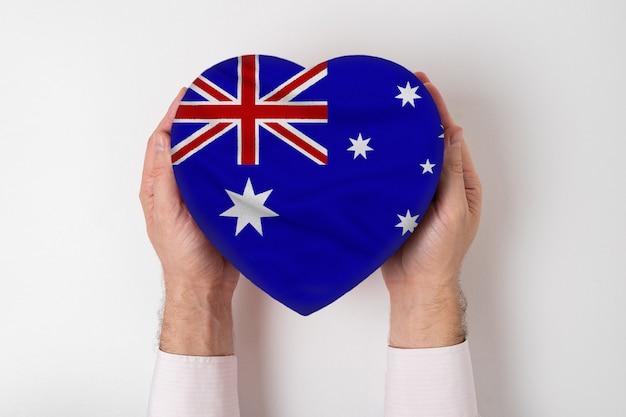 Bandera de australia en una caja en forma de corazón en manos masculinas.