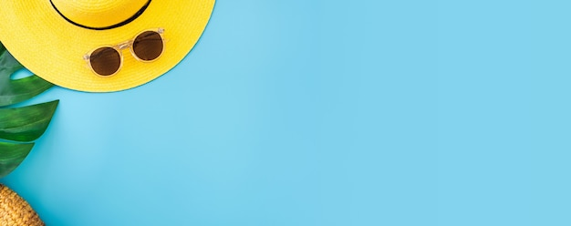 Bandera azul de verano con sombrero amarillo, gafas de sol y hojas de monstera en azul