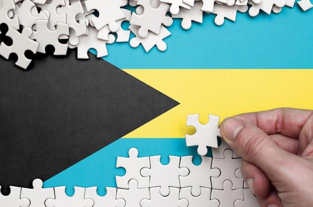 La bandera de bahamas está representada en una mesa en la que la mano humana dobla un rompecabezas de color blanco.