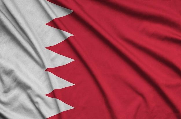 La bandera de bahrein está representada en una tela de tela deportiva con muchos pliegues.