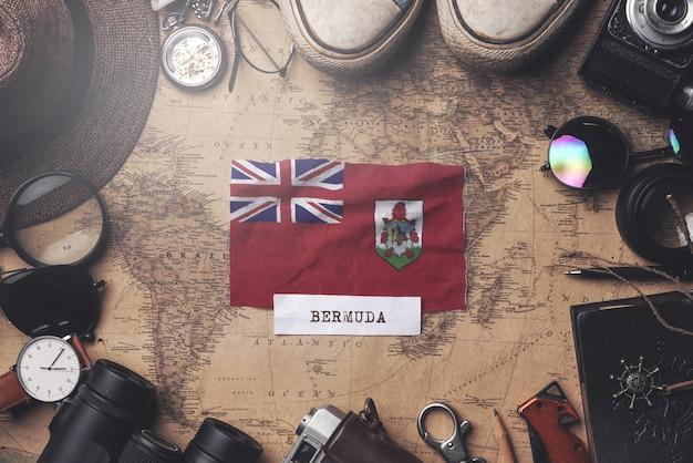 Bandera de las bermudas entre los accesorios del viajero en el mapa antiguo de la vendimia. tiro de arriba