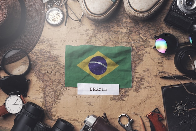 Bandera de brasil entre los accesorios del viajero en el viejo mapa vintage. tiro de arriba