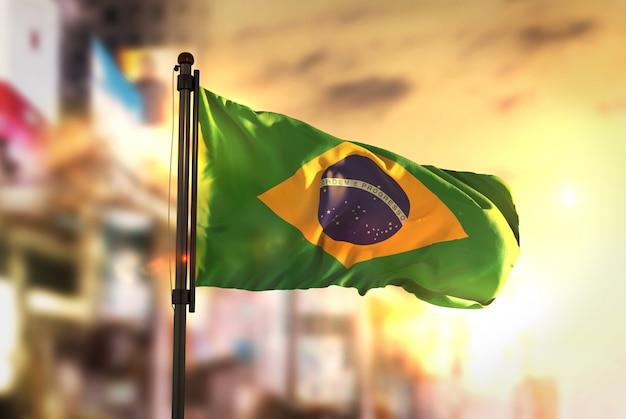 Bandera de brasil contra la ciudad de fondo borrosa a la salida del sol