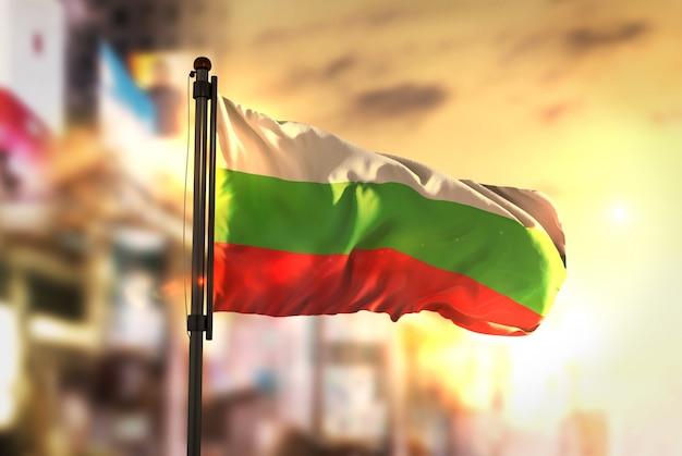 Bandera de bulgaria contra la ciudad de fondo borrosa a la salida del sol