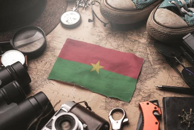 Bandera de burkina faso entre los accesorios del viajero en el viejo mapa vintage. concepto de destino turístico.