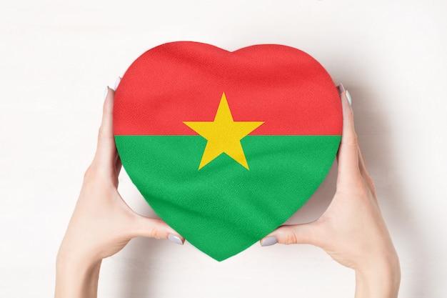 Bandera de burkina faso en una caja en forma de corazón en manos femeninas.