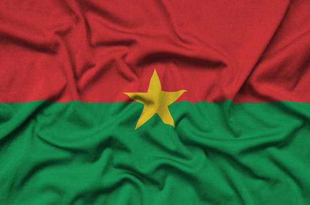 La bandera de burkina faso está representada en una tela de tela deportiva con muchos pliegues.