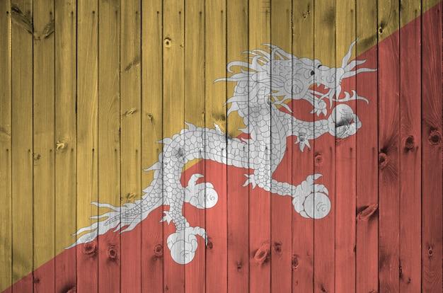 Bandera de bután representada en colores de pintura brillante en la pared de madera vieja.