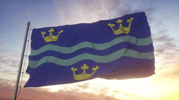 Bandera de cambridgeshire, inglaterra, ondeando en el fondo del viento, el cielo y el sol. representación 3d.