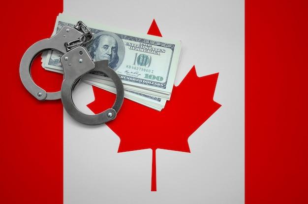 Bandera de canadá con esposas y un fajo de dólares. el concepto de violar la ley y los delitos de ladrones