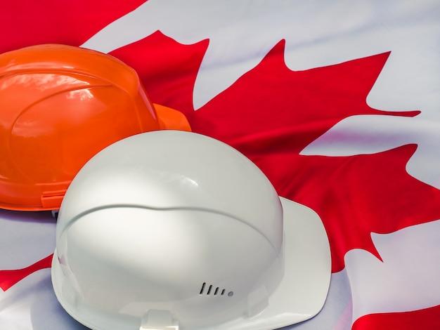 Bandera canadiense y dos cascos protectores. de cerca
