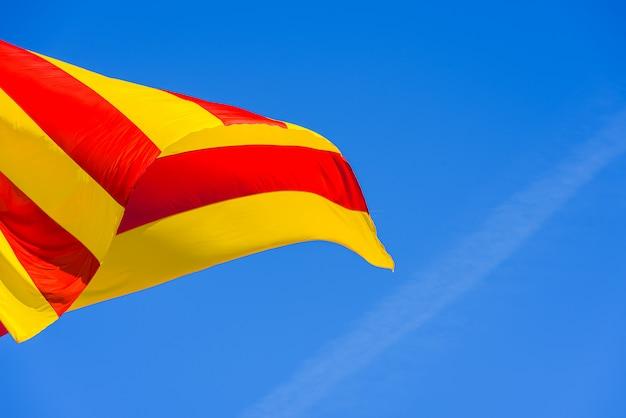 Bandera de cataluña y valencia ondeando con sus franjas rojas y amarillas en el viento.