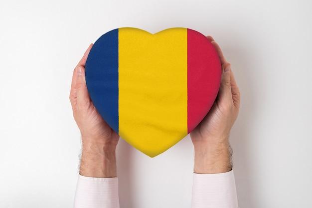 Bandera de chad en una caja en forma de corazón en manos masculinas.