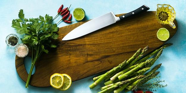 Bandera del chef del cuchillo del chef en una tabla de cortar con hierbas aromáticas y verduras. fondo de alimentos.
