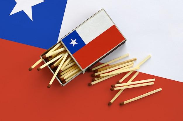 La bandera de chile se muestra en una caja de fósforos abierta, de la cual caen varios partidos y se encuentra en una bandera grande