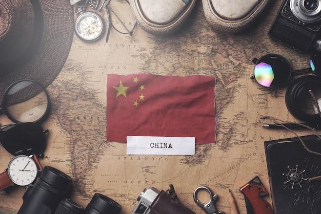 Bandera de china entre los accesorios del viajero en el viejo mapa vintage. tiro de arriba