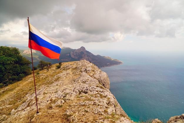 La bandera en la cima del monte kush-kaya crimea. rusia.