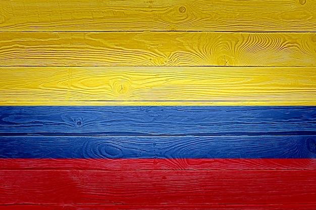 Bandera de colombia pintada sobre fondo de tablón de madera antiguo