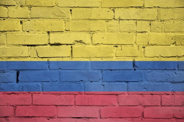 La bandera de colombia está pintada en una vieja pared de ladrillos