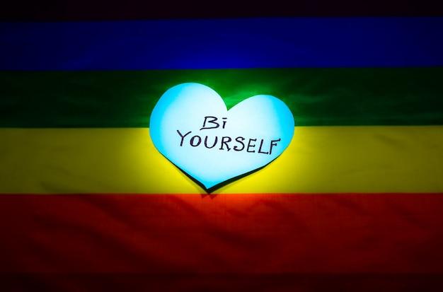 Bandera colorida de la comunidad lgbt. bi usted mismo firma en corazones sobre fondo de arco iris. problemas de lesbianas, gays y bisexuales. legalización del matrimonio para parejas con orientación homosexual.