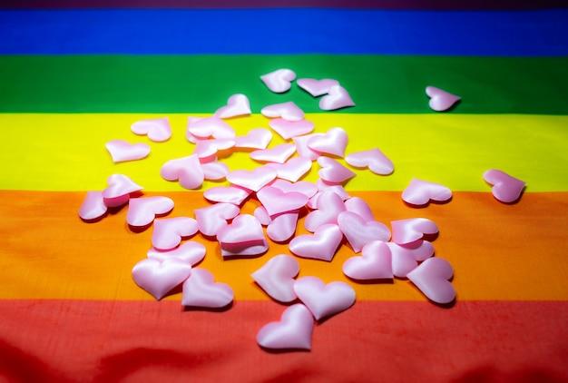 Bandera colorida de la comunidad lgbt. corazón de corazones de color rosa sobre fondo de arco iris. problemas de lesbianas y gays. legalización del matrimonio para parejas con orientación homosexual.