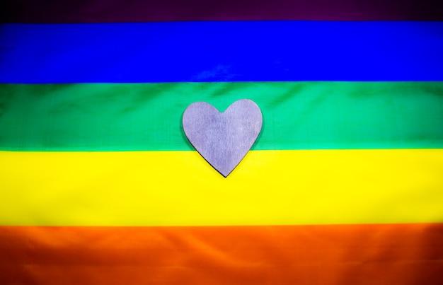 Bandera colorida de la comunidad lgbt. corazón de madera sobre fondo de arco iris. problemas de lesbianas y gays. legalización del matrimonio para pareja con orientación homosexual.
