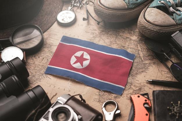 Bandera de corea del norte entre los accesorios del viajero en el viejo mapa vintage. concepto de destino turístico.