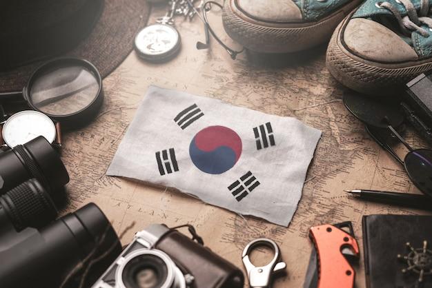 Bandera de corea del sur entre los accesorios del viajero en el viejo mapa vintage. concepto de destino turístico.