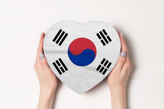 Bandera de corea del sur en una caja en forma de corazón en manos femeninas.