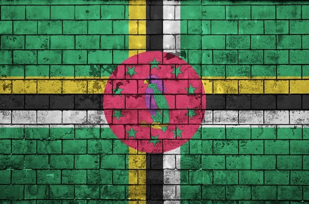 La bandera de dominica está pintada en una vieja pared de ladrillos