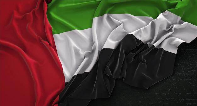 Bandera de los emiratos árabes unidos arrugado sobre fondo oscuro 3d render