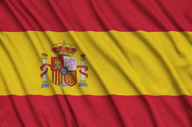La bandera de españa está representada en una tela de tela deportiva con muchos pliegues.