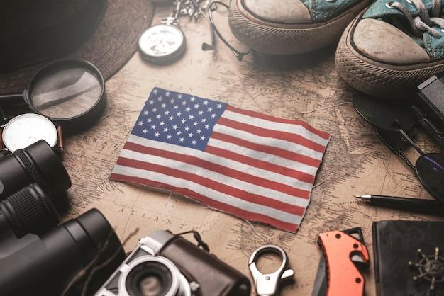 Bandera de los estados unidos de américa entre los accesorios del viajero en el viejo mapa vintage. concepto de destino turístico.